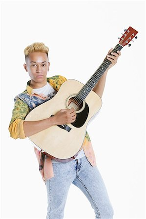 Portrait of a teenage boy playing guitar over gray background Stock Photo - Premium Royalty-Free, Code: 693-06379492