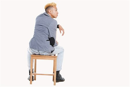 Back view of teenage boy sitting on chair as he looks away over gray background Stock Photo - Premium Royalty-Free, Code: 693-06379517