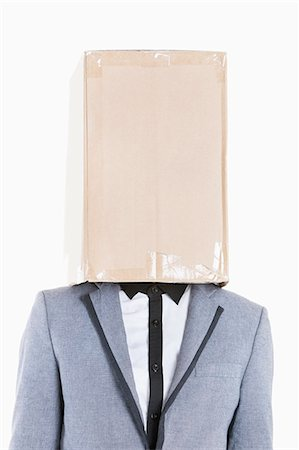 Young boy wearing jacket with box covered over his face on gray background Stock Photo - Premium Royalty-Free, Code: 693-06379518