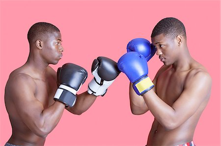 Side view of two African American boxers in fighting stance over pink background Stock Photo - Premium Royalty-Free, Code: 693-06379527