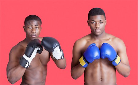 Portrait of two African American boxers wearing gloves over red background Stock Photo - Premium Royalty-Free, Code: 693-06379528