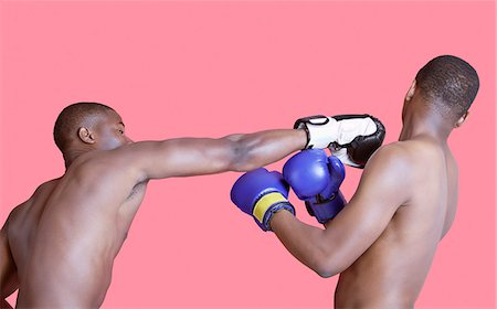 African American boxer punching opponent over pink background Stock Photo - Premium Royalty-Free, Code: 693-06379529