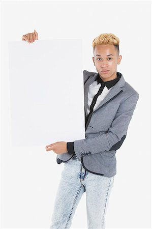 Portrait of a young man holding blank cardboard over gray background Stock Photo - Premium Royalty-Free, Code: 693-06379521