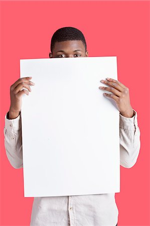 Portrait of a young man holding blank cardboard in front of face over pink background Stock Photo - Premium Royalty-Free, Code: 693-06379533