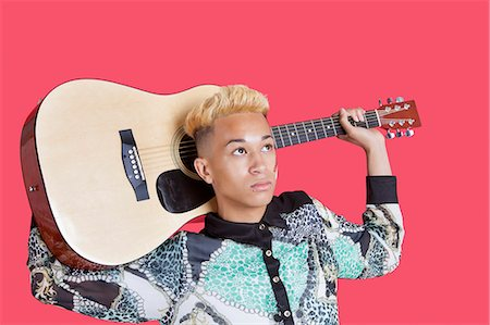 Teenage boy carrying guitar over his shoulder over pink background Stock Photo - Premium Royalty-Free, Code: 693-06379552