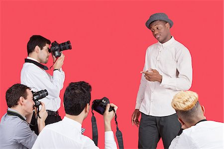 Paparazzi taking photographs of male actor over red background Stock Photo - Premium Royalty-Free, Code: 693-06379565