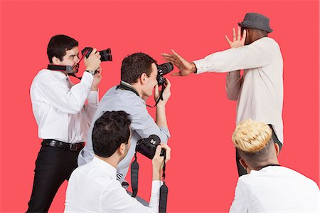 Young male celebrity shielding face from photographers over red background Stock Photo - Premium Royalty-Free, Code: 693-06379566