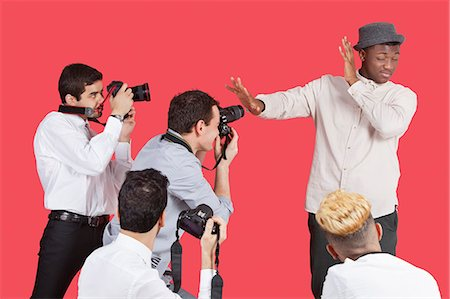 Young male celebrity shielding face from photographers over red background Stock Photo - Premium Royalty-Free, Code: 693-06379567