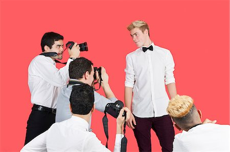 Paparazzi taking photographs of male actor over red background Stock Photo - Premium Royalty-Free, Code: 693-06379568