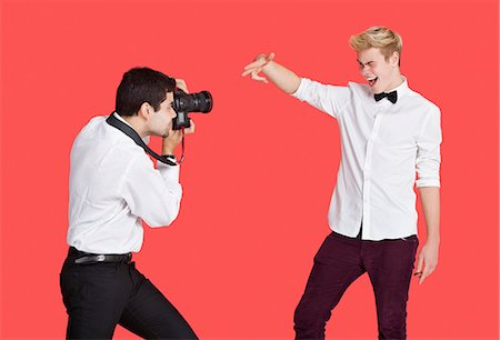 Male actor being photographed by paparazzi over red background Stock Photo - Premium Royalty-Free, Code: 693-06379561