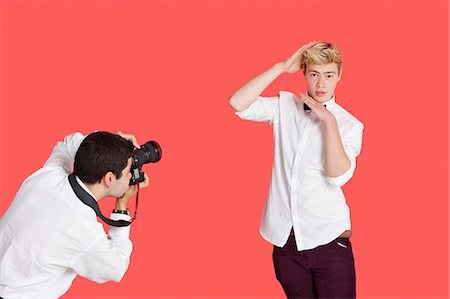 Male actor being photographed by paparazzi over red background Stock Photo - Premium Royalty-Free, Code: 693-06379562