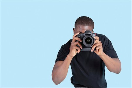 African American young man taking photo through digital camera over blue background Stock Photo - Premium Royalty-Free, Code: 693-06379576