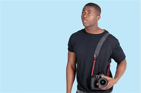 Young African American man with digital camera looking up over blue background Stock Photo - Premium Royalty-Free, Code: 693-06379577