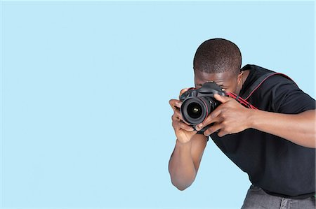 Young man taking photo through digital camera over blue background Stock Photo - Premium Royalty-Free, Code: 693-06379578
