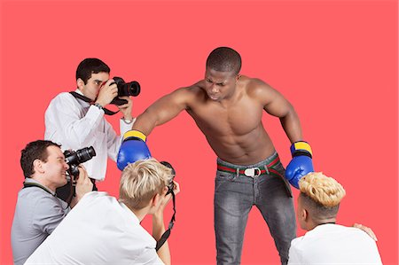 Paparazzi taking photographs of male boxer over red background Stock Photo - Premium Royalty-Free, Code: 693-06379570