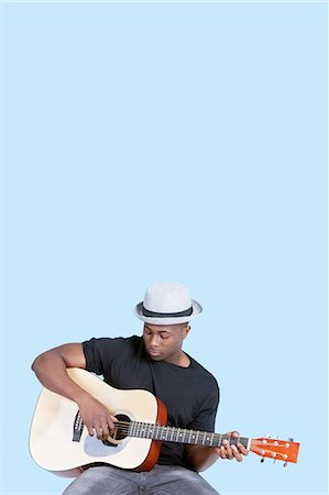 Young African American man playing guitar over light blue background Stock Photo - Premium Royalty-Free, Code: 693-06379571