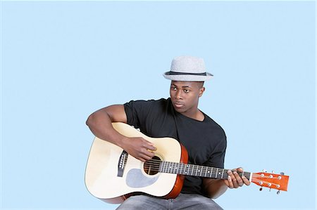 Young African American man playing guitar over light blue background Stock Photo - Premium Royalty-Free, Code: 693-06379572