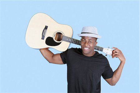 Portrait of a young African American man carrying guitar over light blue background Stock Photo - Premium Royalty-Free, Code: 693-06379573