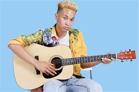 Portrait of a young teenage boy playing guitar over blue background Stock Photo - Premium Royalty-Free, Code: 693-06379584