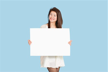 Portrait of a beautiful young woman holding blank cardboard over blue background Stock Photo - Premium Royalty-Free, Code: 693-06379589