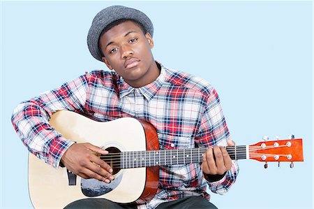 Portrait of a young man playing guitar over light blue background Stock Photo - Premium Royalty-Free, Code: 693-06379581