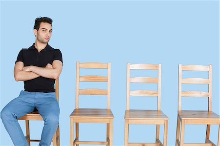 Portrait of a young man sitting beside empty wooden chairs over blue background Stock Photo - Premium Royalty-Free, Code: 693-06379590