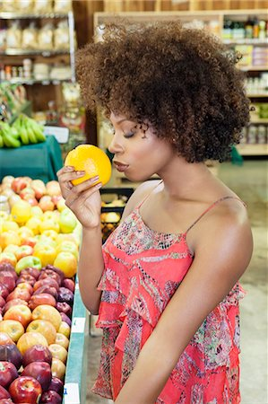 sale - Side view of African American woman smelling fresh orange at supermarket Stock Photo - Premium Royalty-Free, Code: 693-06379618