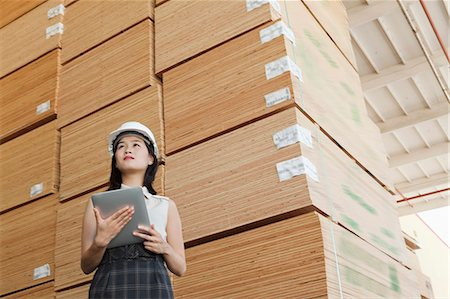 Low angle view of female industrial worker holding tablet PC with stacked wooden planks in background Stock Photo - Premium Royalty-Free, Code: 693-06379671