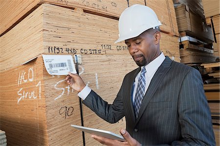 African American male contractor using tablet PC while inspecting wooden planks Stock Photo - Premium Royalty-Free, Code: 693-06379710
