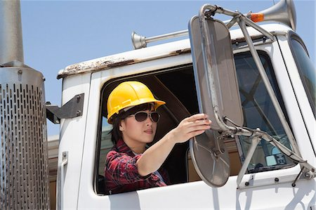 female truck driver - Asian female industrial worker adjusting mirror while sitting in logging truck Stock Photo - Premium Royalty-Free, Code: 693-06379728