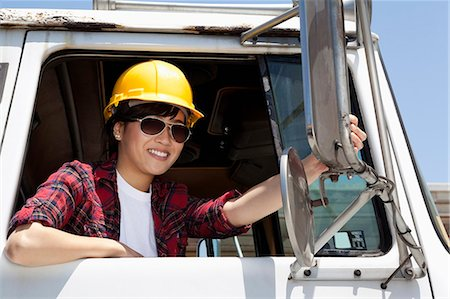 female truck driver - Female industrial worker adjusting mirror while sitting in logging truck Stock Photo - Premium Royalty-Free, Code: 693-06379729