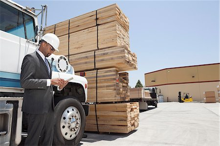 African American male contractor using tablet PC while standing by logging truck Stock Photo - Premium Royalty-Free, Code: 693-06379723