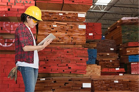 piles of work - Side view of an Asian female industrial worker working on tablet PC with stacked wooden planks in background Stock Photo - Premium Royalty-Free, Code: 693-06379734