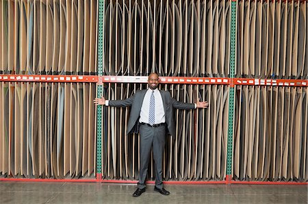 Portrait of happy African American businessman standing arms outstretched in front of thin veneer sheets Stock Photo - Premium Royalty-Free, Code: 693-06379751