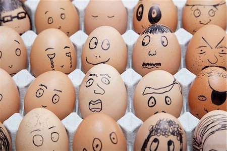 Funny faces on painted on brown eggs arranged in carton Stock Photo - Premium Royalty-Free, Code: 693-06379764