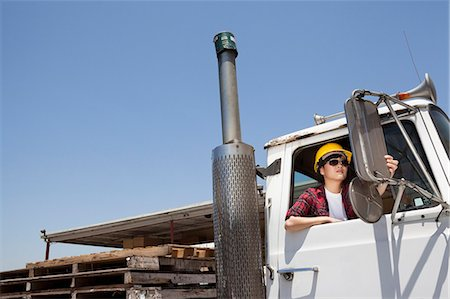 female truck driver - Female industrial worker adjusting mirror while sitting in logging truck Stock Photo - Premium Royalty-Free, Code: 693-06379761