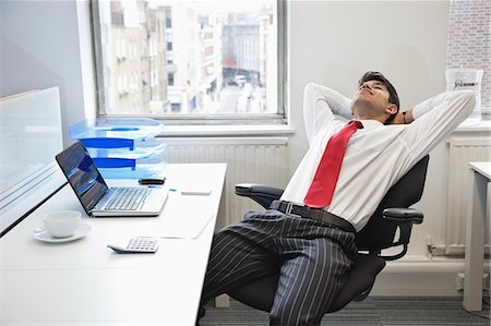 east indian (male) - Young Indian businessman relaxing in chair at office desk Stock Photo - Premium Royalty-Free, Code: 693-06379786