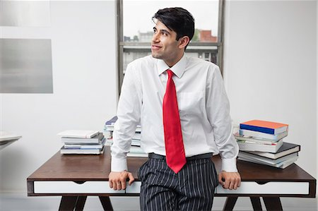 east indian (male) - Indian businessman leaning on desk while looking away in office Stock Photo - Premium Royalty-Free, Code: 693-06379801