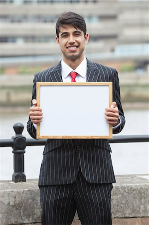 Portrait of young Indian businessman holding blank sign Stock Photo - Premium Royalty-Free, Code: 693-06379813