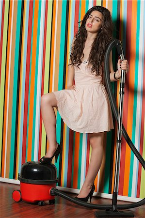 Portrait of young woman with vacuum cleaner standing against colorful striped wall Stock Photo - Premium Royalty-Free, Code: 693-06379845