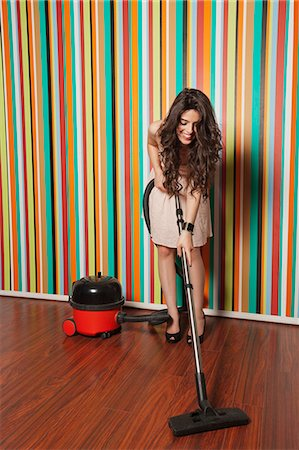 Happy young woman cleaning hardwood floor using vacuum cleaner Stock Photo - Premium Royalty-Free, Code: 693-06379846