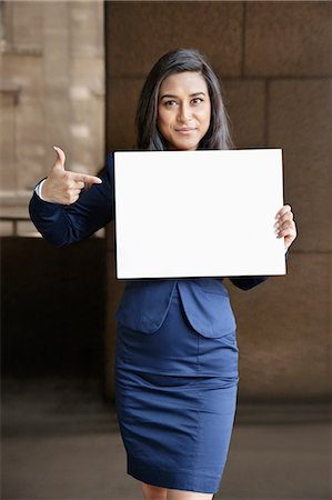 person holding sign - Portrait of a young Indian businesswoman pointing towards Moodboard sign Stock Photo - Premium Royalty-Free, Code: 693-06379886