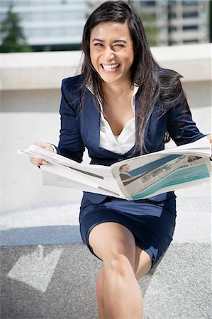 Portrait of a laughing Indian businesswoman with newspaper sitting outdoors Stock Photo - Premium Royalty-Free, Code: 693-06379889