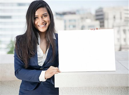 sign - Portrait of a young Indian businesswoman holding Moodboard sign Stock Photo - Premium Royalty-Free, Code: 693-06379894