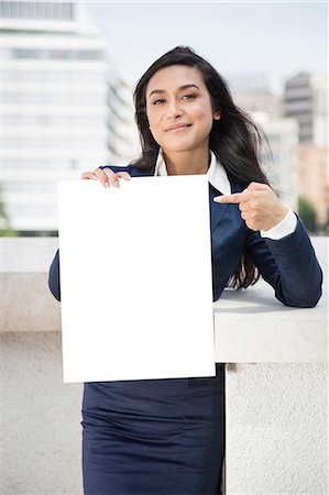 staff - Portrait of a young Indian businesswoman pointing towards Moodboard sign Stock Photo - Premium Royalty-Free, Code: 693-06379895