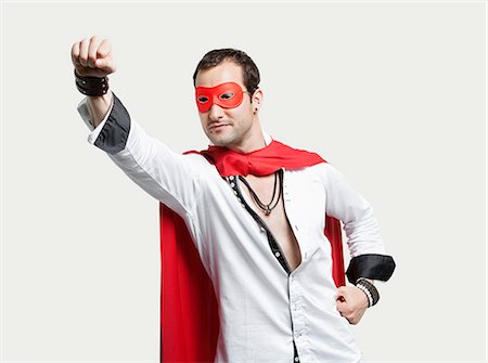 Young man wearing superhero costume against gray background Stock Photo - Premium Royalty-Free, Code: 693-06379908