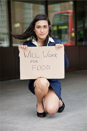 Young Indian businesswoman holding 'Will Work for Food' sign Stock Photo - Premium Royalty-Free, Code: 693-06379902