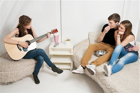 Young woman playing guitar with friends sitting on sofa Stock Photo - Premium Royalty-Free, Code: 693-06379926