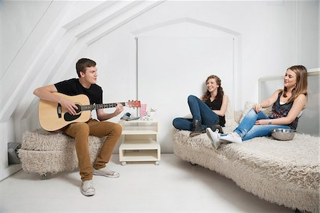 Young man playing guitar with female friends sitting on sofa Stock Photo - Premium Royalty-Free, Code: 693-06379928
