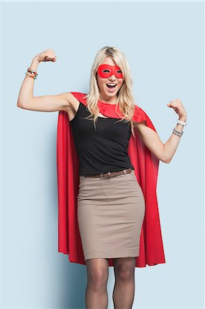 superhero costume - Portrait of excited young blond woman in superhero costume flexing arms over light blue background Stock Photo - Premium Royalty-Free, Code: 693-06379994